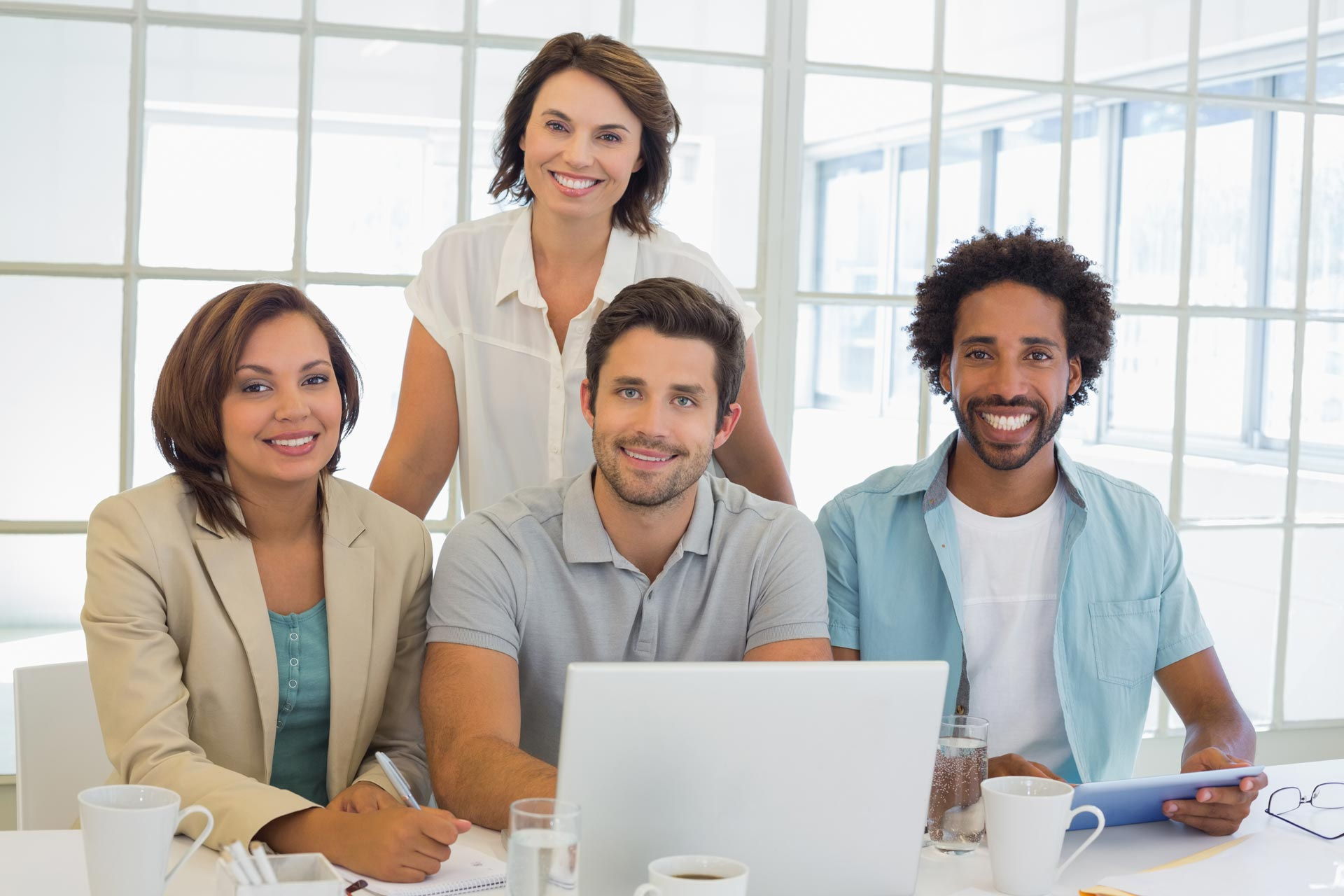 Portrait-of-four-smiling-young-business-people-using-laptop ...